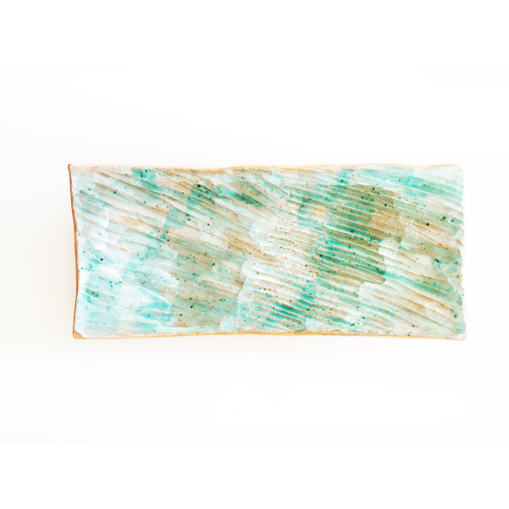 Surface design in green on ceramic tray