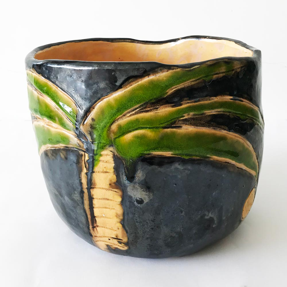Blue ceramic plant pot with green palm leafs